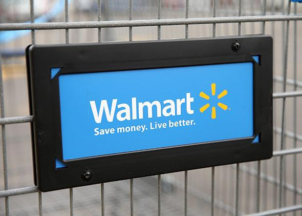 The Walmart logo is displayed on a shopping cart at a Walmart store.