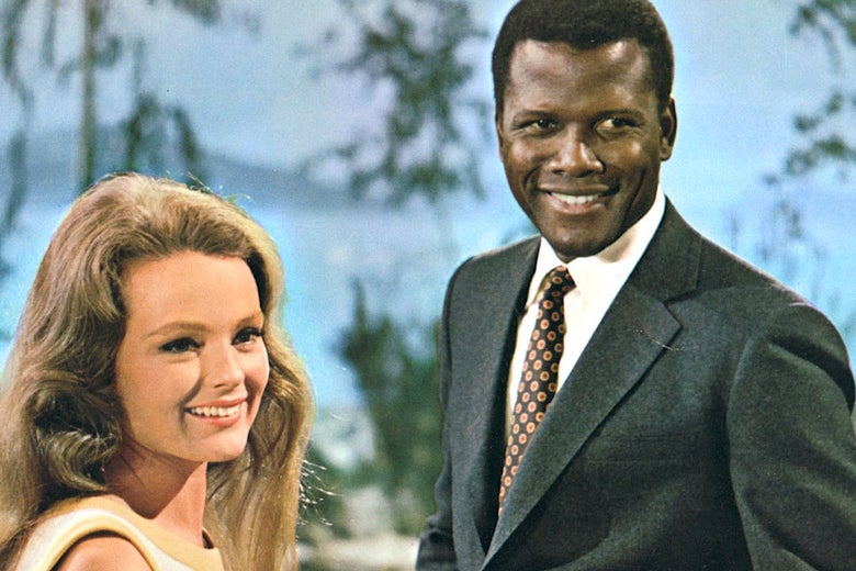 A white woman with brown hair stands next to a black man with a suit and tie on.