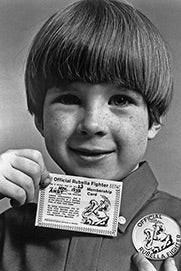 """A kid carries an """"Official Rubella Fighter"""" card and wears a button with the same phrase."""