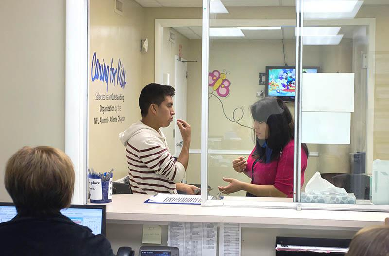 Yessi Navarro assisting a Spanish speaking patient in the patient waiting area.
