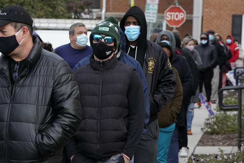 A line of people in winter clothes and face masks.