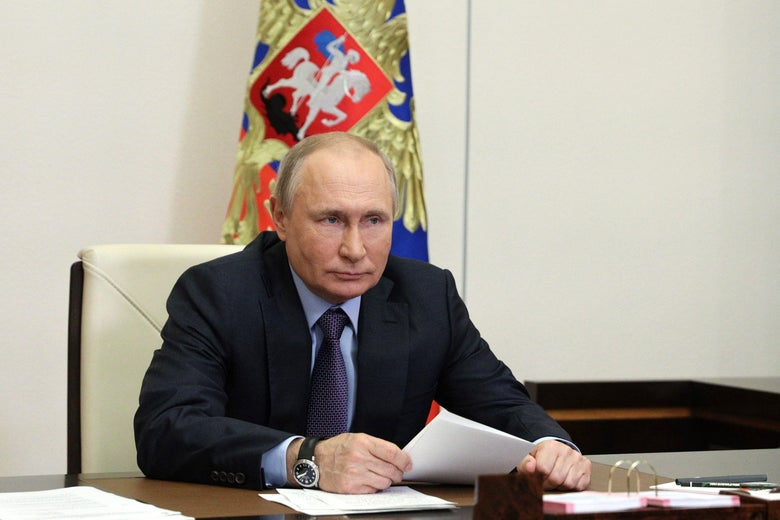 Vladimir Putin sits at a table holding a piece of paper, with a flag behind him.