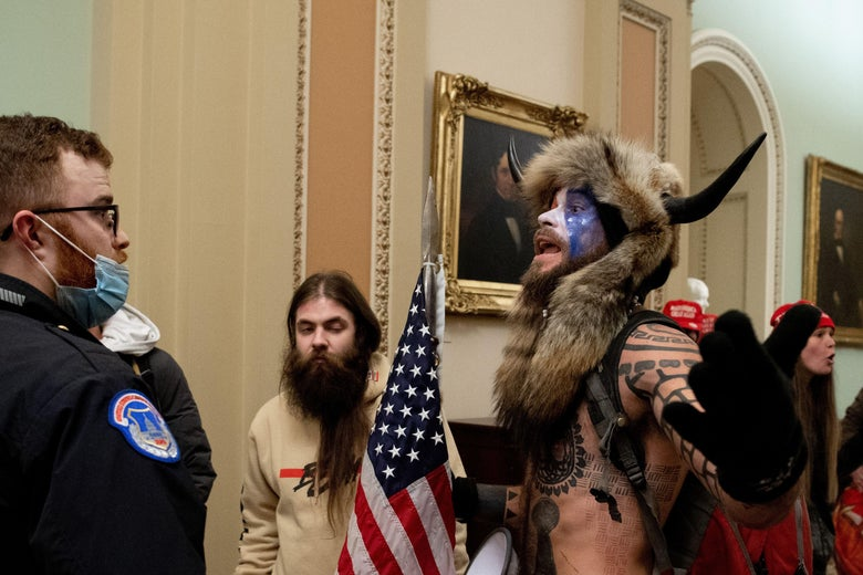 A shirtless man wearing red, white, and blue face paint, a horned hat, and a fur headdress addresses a Capitol Police officer. Beside the shirtless man is a man with long hair and a beard holding an American flag. In the background are more people wearing MAGA hats.