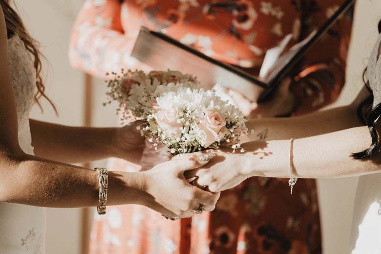 Two pairs of women's hands clasp a bouquet together, in front of a torso of a person holding a binder.