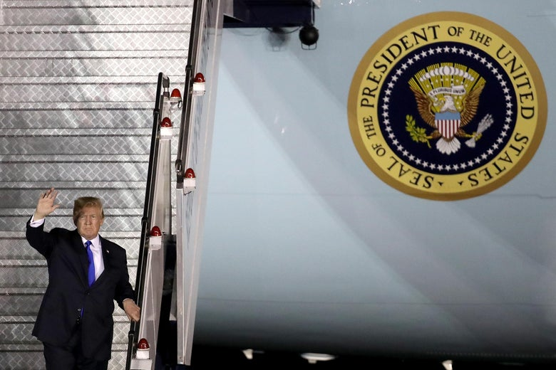 Donald Trump waves as he descends the stairs down from Air Force One.