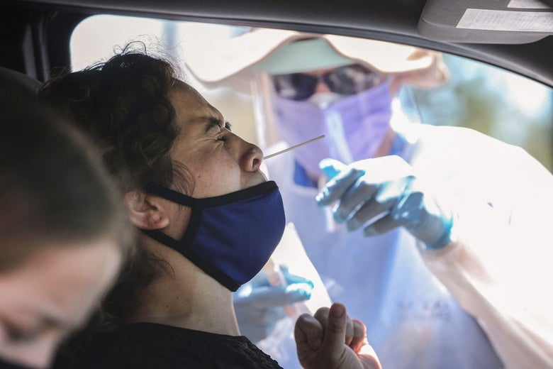 A health care worker helps a person in a car get a nasal swab COVID-19 test.
