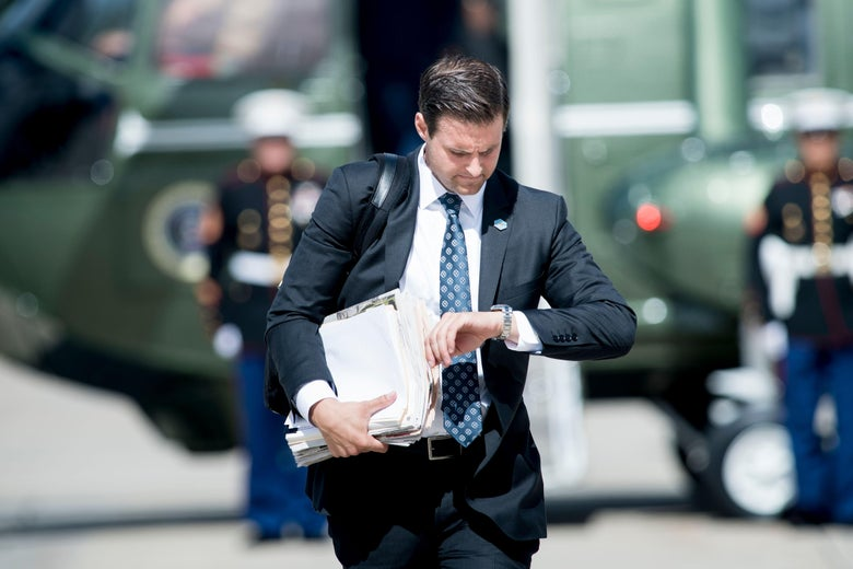 John McEntee checks his watch while holding file folders and papers in his other arm.
