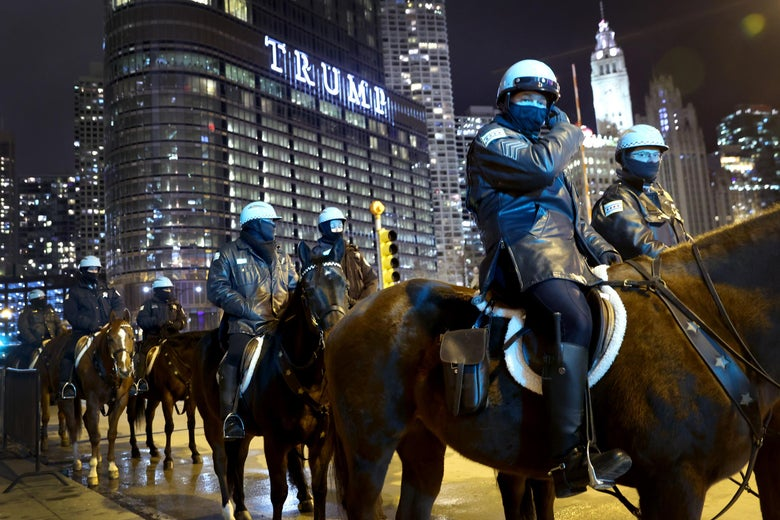 Police on horseback in Chicago monitor protests near Trump Tower in the background.