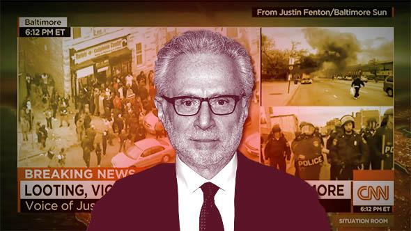 TV personality Wolf Blitzer attends the Soul Train Awards 2013 in November 2013 in Las Vegas, Nevada. Behind, CNN's live feed of Baltimore on the Situation Room.