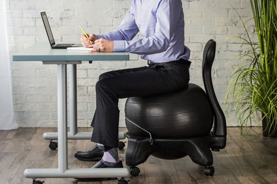 Man sitting on an exercise ball chair.