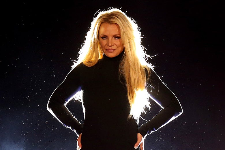 Britney Spears looking pensive onstage in a black dress with her hands on her hips facing the audience