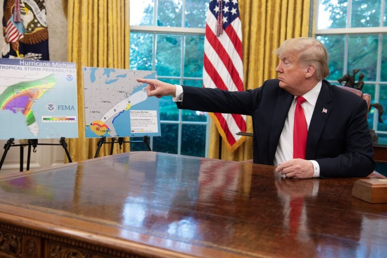 Donald Trump, seated in the Oval Office in front of yellow drapes, points at a poster-board map.