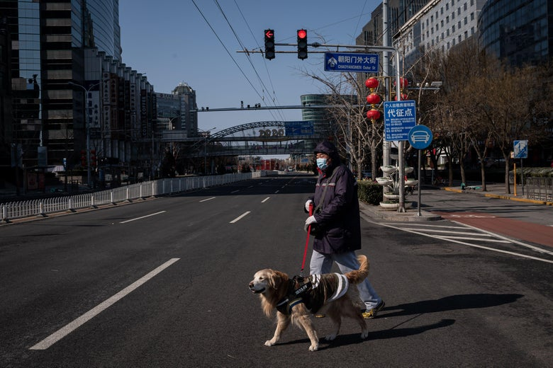 A man wearing a protective face mask walks his dog as he cross a nearly empty street in Beijing on February 15, 2020.