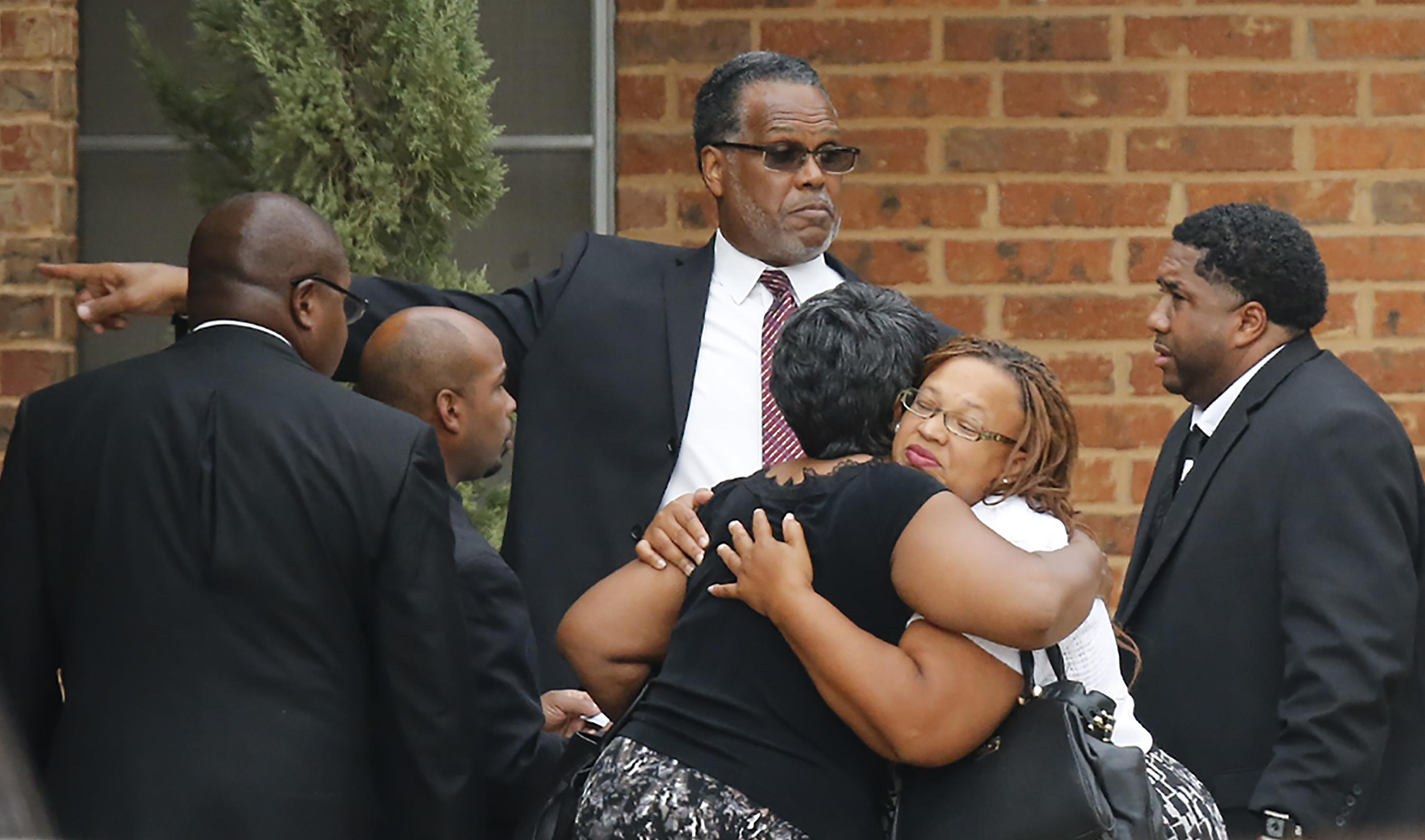 Two women, dressed in funeral clothes, embrace. A man in a suit directs people toward the service.