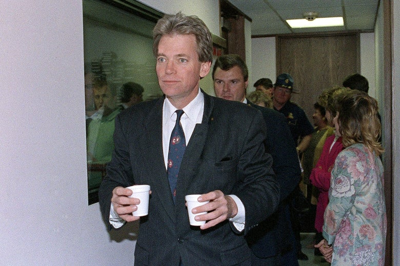David Duke carrying two little styrofoam cups. A radio studio is seen, along with people milling about, behind him.