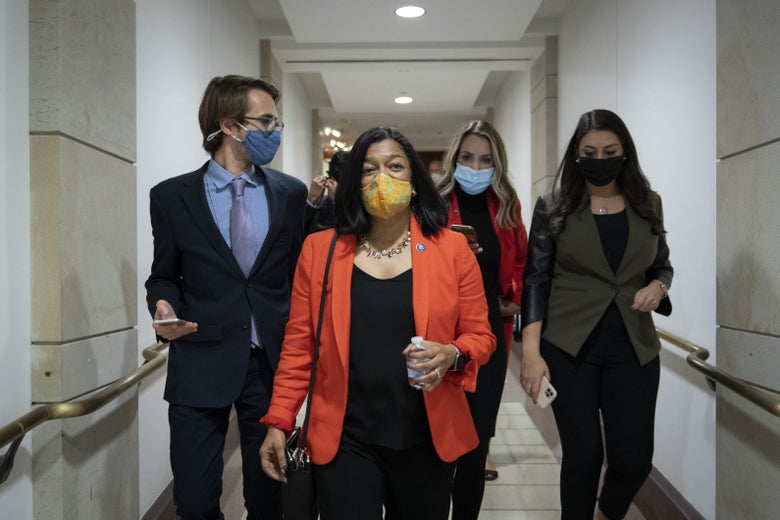 Jayapal walking down a hallway with a few other people