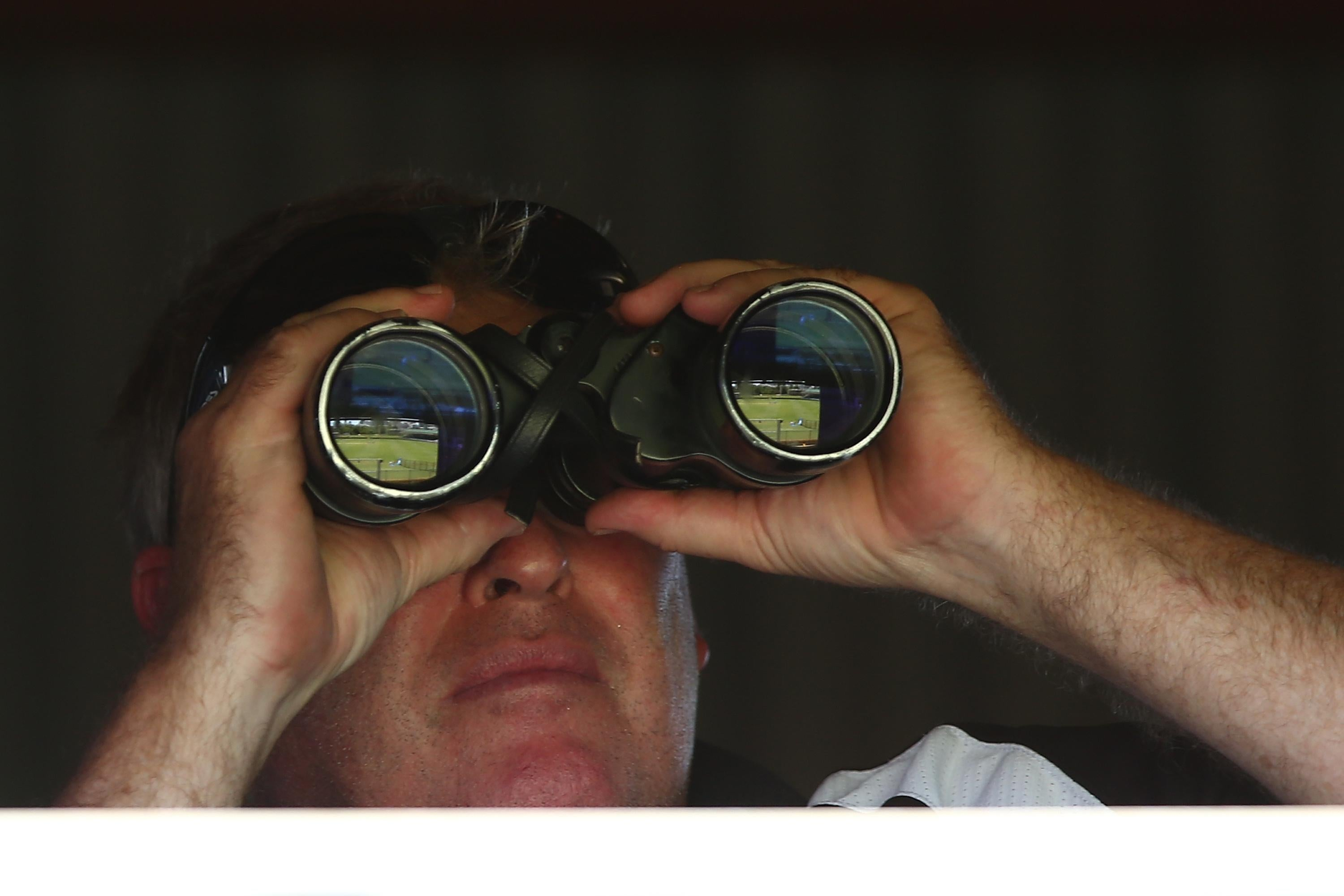 Man looking through a pair of binoculars.