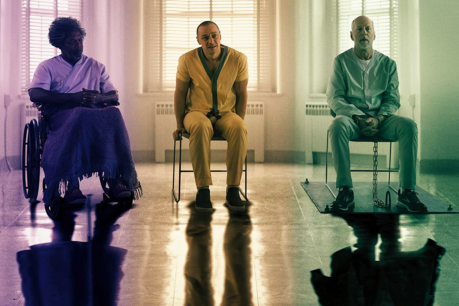Bruce Willis, Samuel L. Jackson, and James McAvoy in Glass. The three men are seated next to each other in what appears to be a mental hospital.