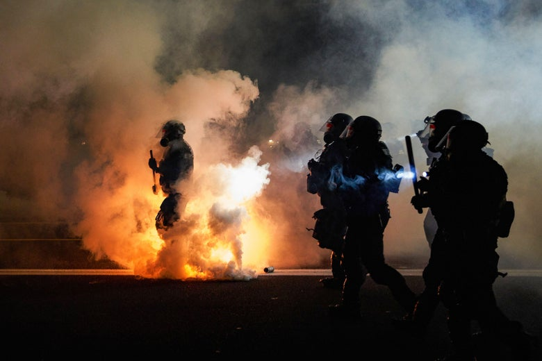 Police wearing riot gear and holding batons walk through tear gas at night