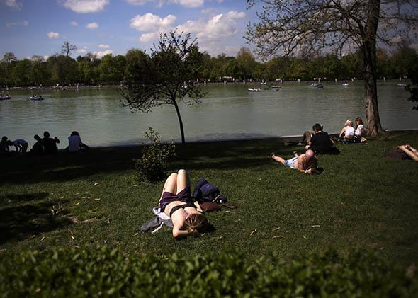People sunbathe and watch boats on an artificial lake as they enjoy the warm weather during a sunny spring day at Madrid's Retiro park