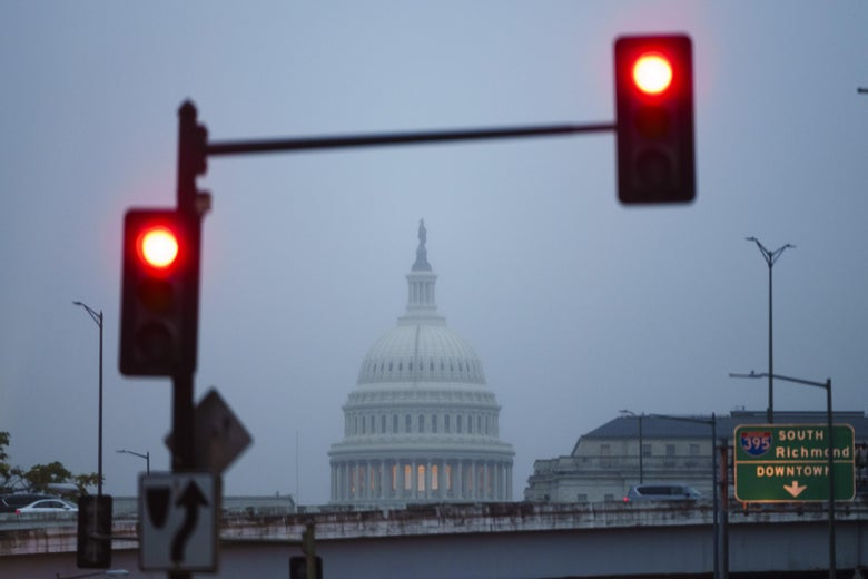 Capitol dome seen from a distance on a foggy morning, with red stoplights in the foreground