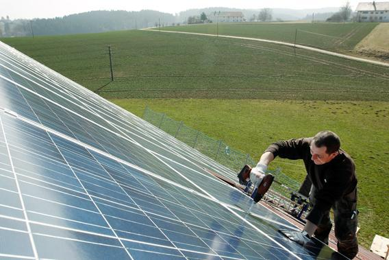 A worker mounts 320 square metres of solar panels on the roof of a farmstead barn in Binsham near Landshut March 21, 2012.