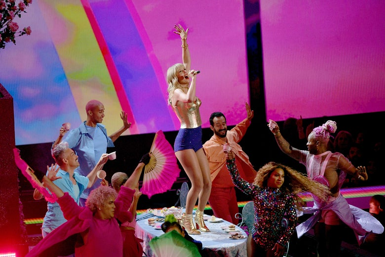 Taylor Swift performs in glittery clothes, surrounded by backup dancers.