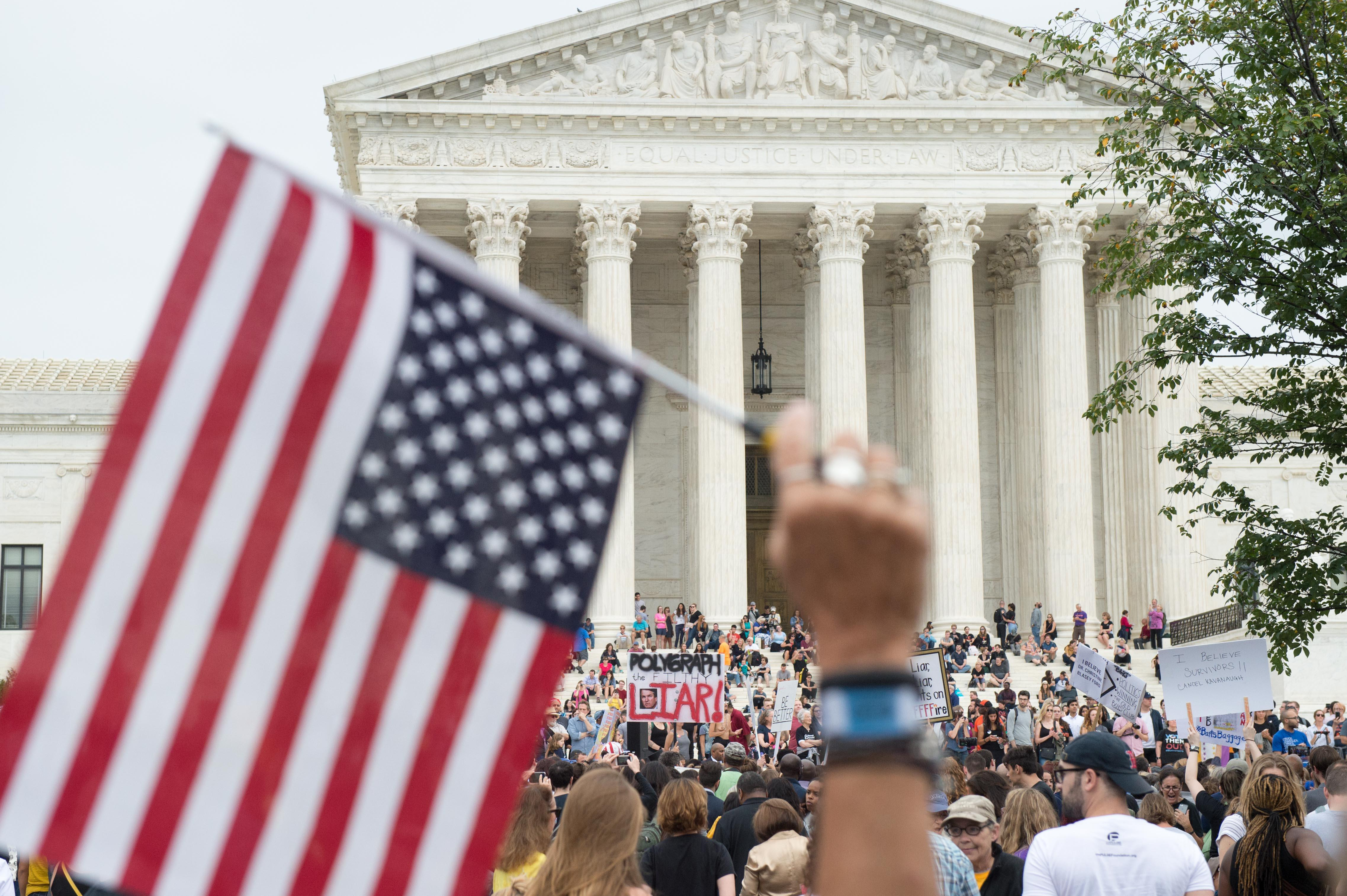 A crowd of protesters gather and hold signs in front of the Supreme Court building. In the foreground a hand holds up an American flag.