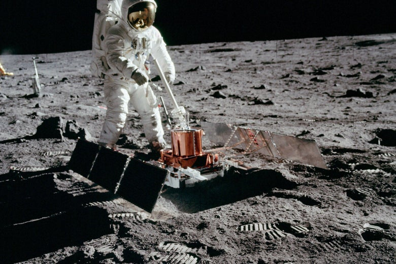 Apollo 11 astronaut Buzz Aldrin with the seismic experiment. Solar panels have deployed on the left and right and the antenna is pointed at Earth. The laser reflector is beyond the antenna and, in the distance, the TV camera is silhouetted against the black sky.