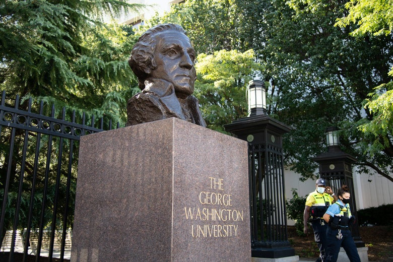 A statue out front of a gate entering GW University.