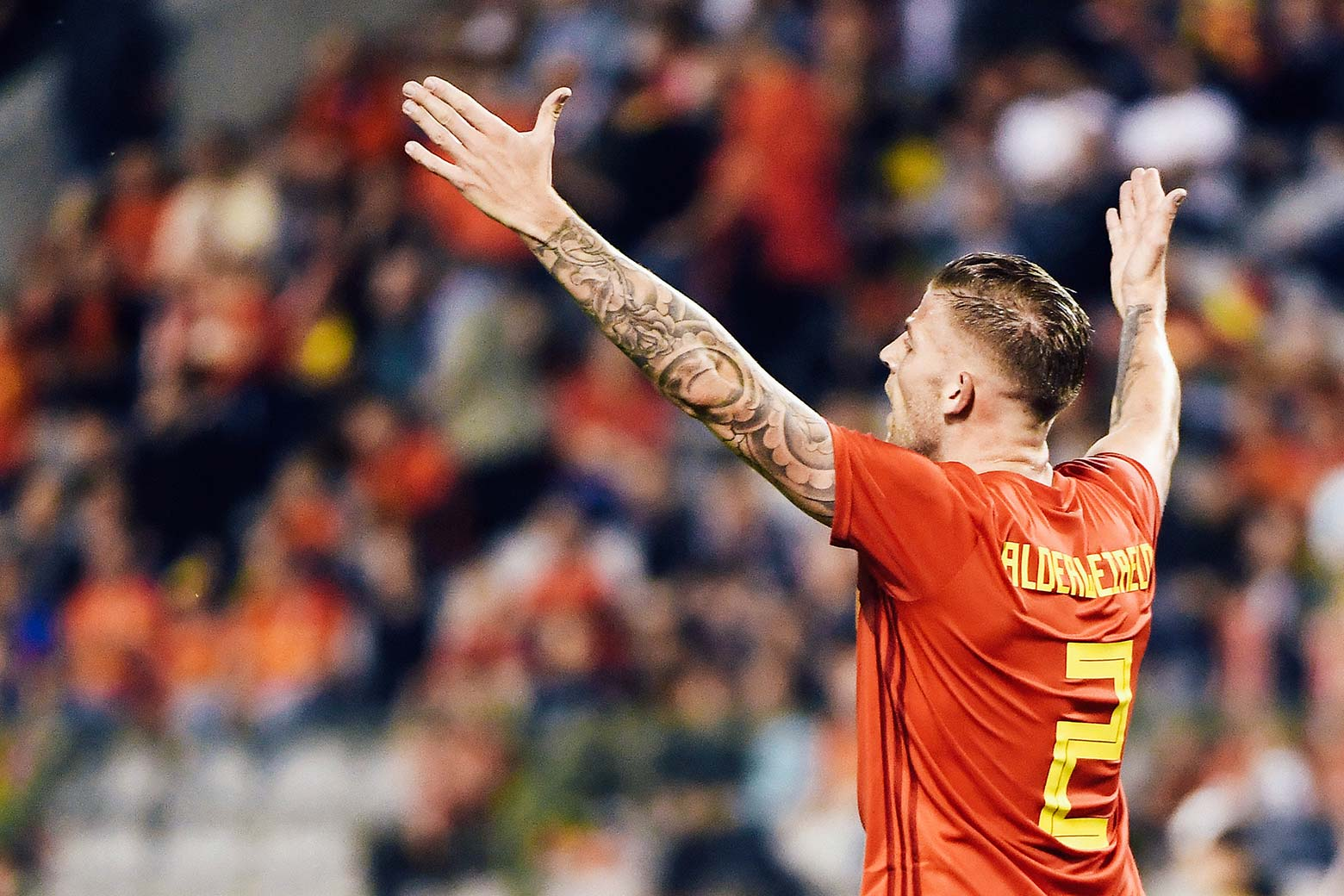 Toby Alderweireld holds up his tattooed arms while on the field.