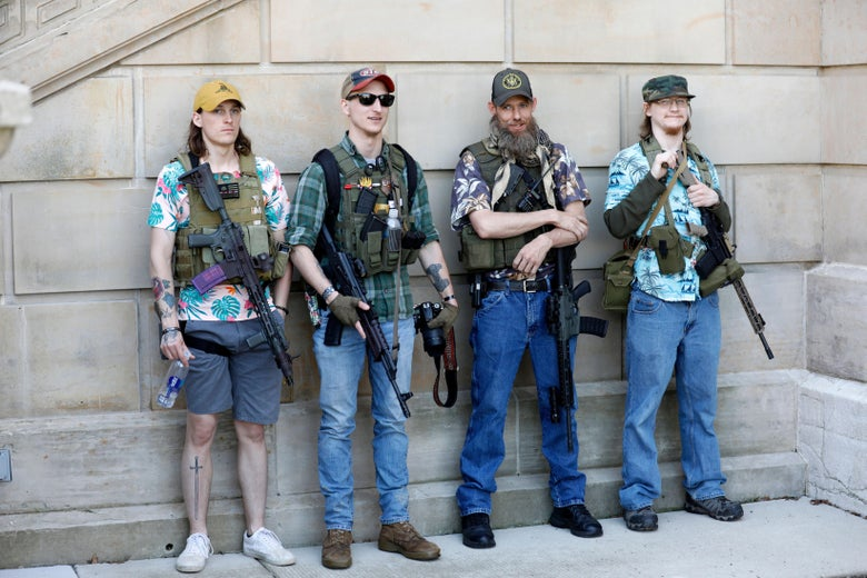 Four Boogaloo Bois carrying rifles and wearing Hawaiian shirts, lined up against a wall.