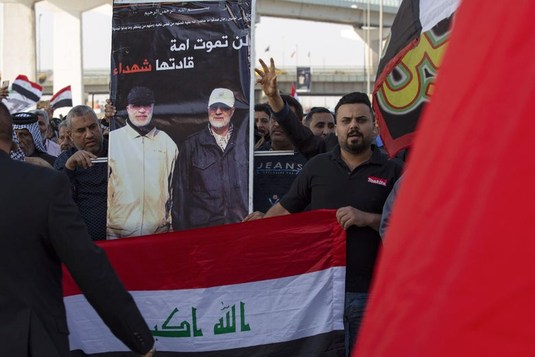 Iraqis carry a poster depicting Iran's Major General Qasem Soleimani (R) and senior Iraqi military figure Abu Mahdi al-Muhandis as they march in a symbolic funeral procession in the southern city of Basra, on January 5, 2020.