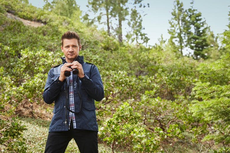 Jeremy Renner stands holding binoculars but again not looking through them.