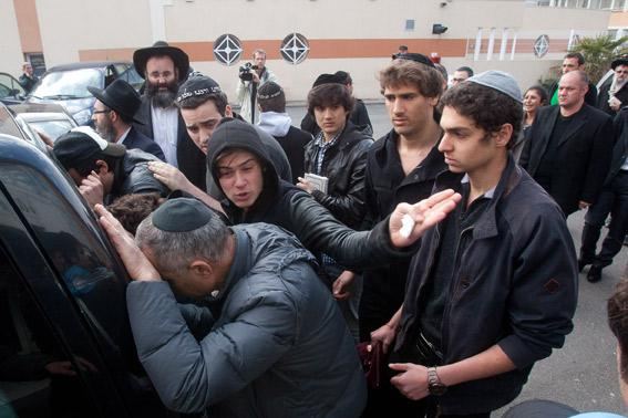 Relatives and mourners attend a ceremony at 'Ozar Hatorah' Jewish school.