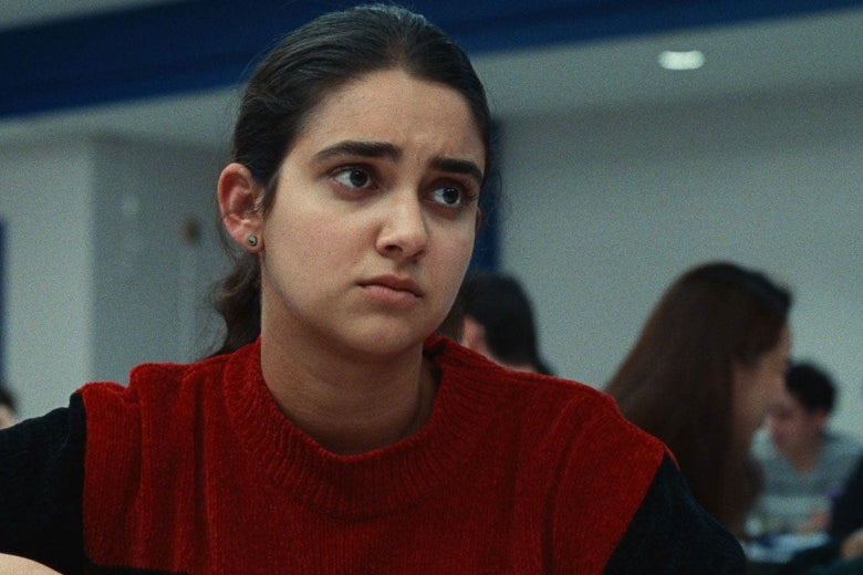 Rachel Bhargava (Geraldine Viswanathan) from the bust up, sitting in a high school cafeteria, in Bad Education.