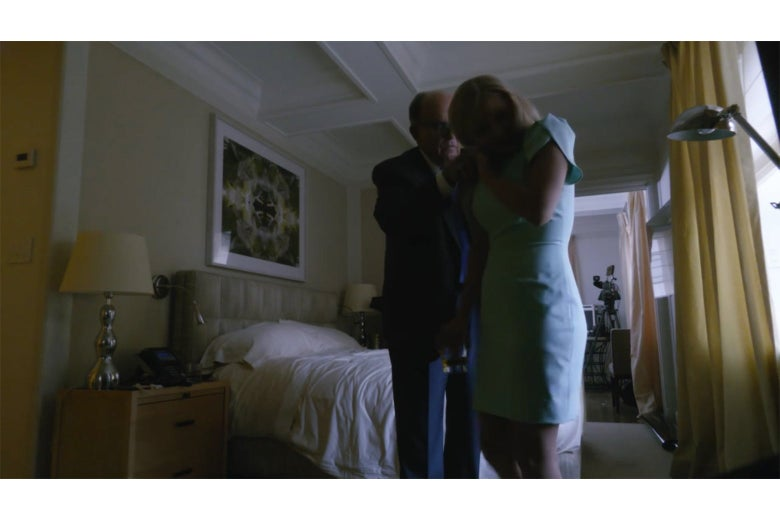 A shot from Borat of a hotel bedroom. Tutar, in a turquoise dress, is closer to the camera, and Rudy Giuliani is touching her shoulder.