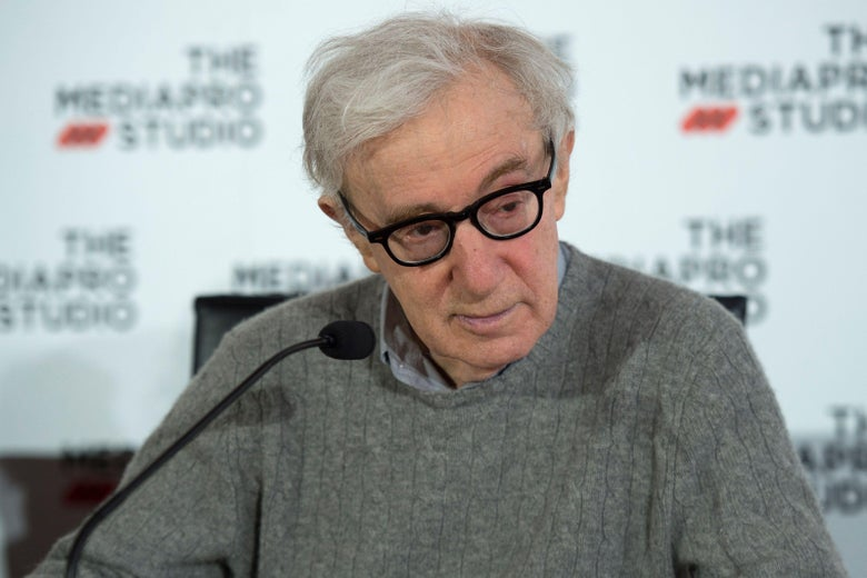 Woody Allen sits behind a microphone, wearing a gray sweater with a collared shirt under it.