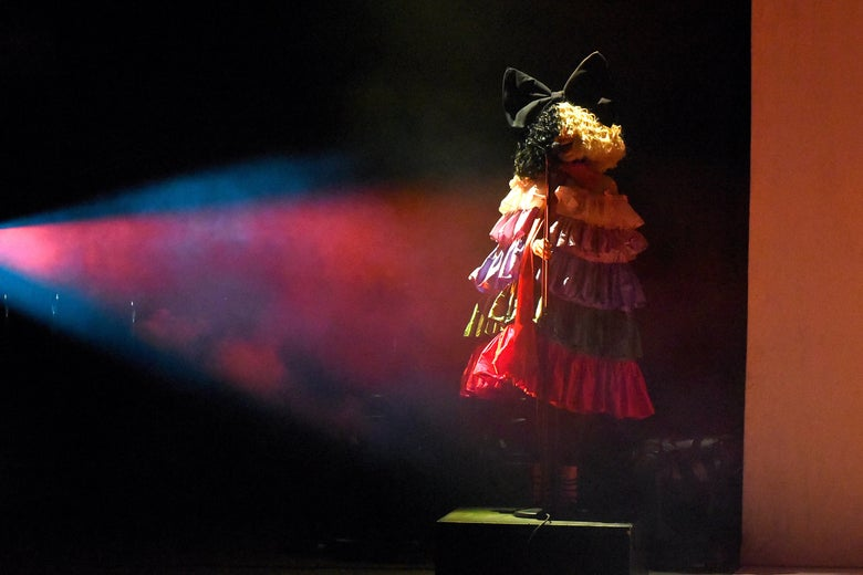 Sia, wearing a multilayered ruffled dress and a large black-and-white wig that covers her entire face, stands alone on a stage.