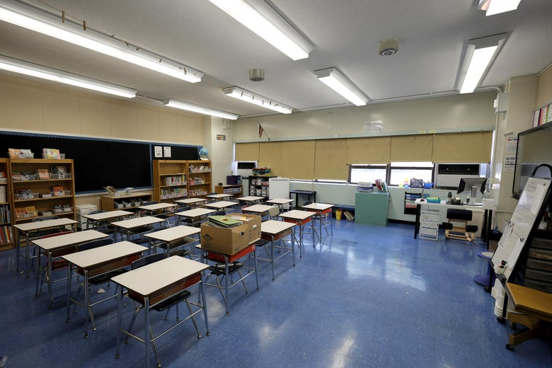 An empty classroom with desks, shelves, and a chalkboard