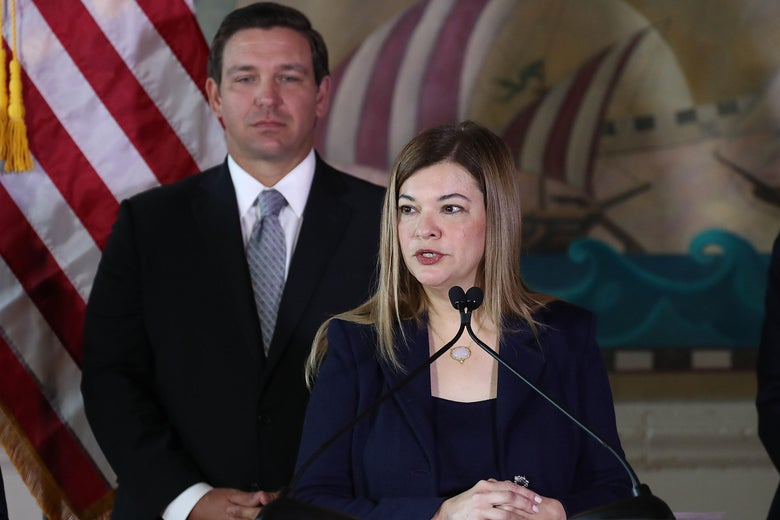 Barbara Lagoa speaks at a podium, with Ron DeSantis standing behind her.