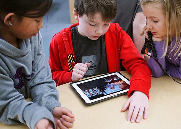 Children use an iPad in the classroom