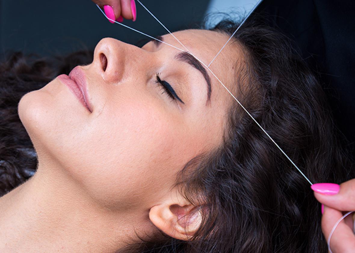 A woman getting her eyebrows threaded.