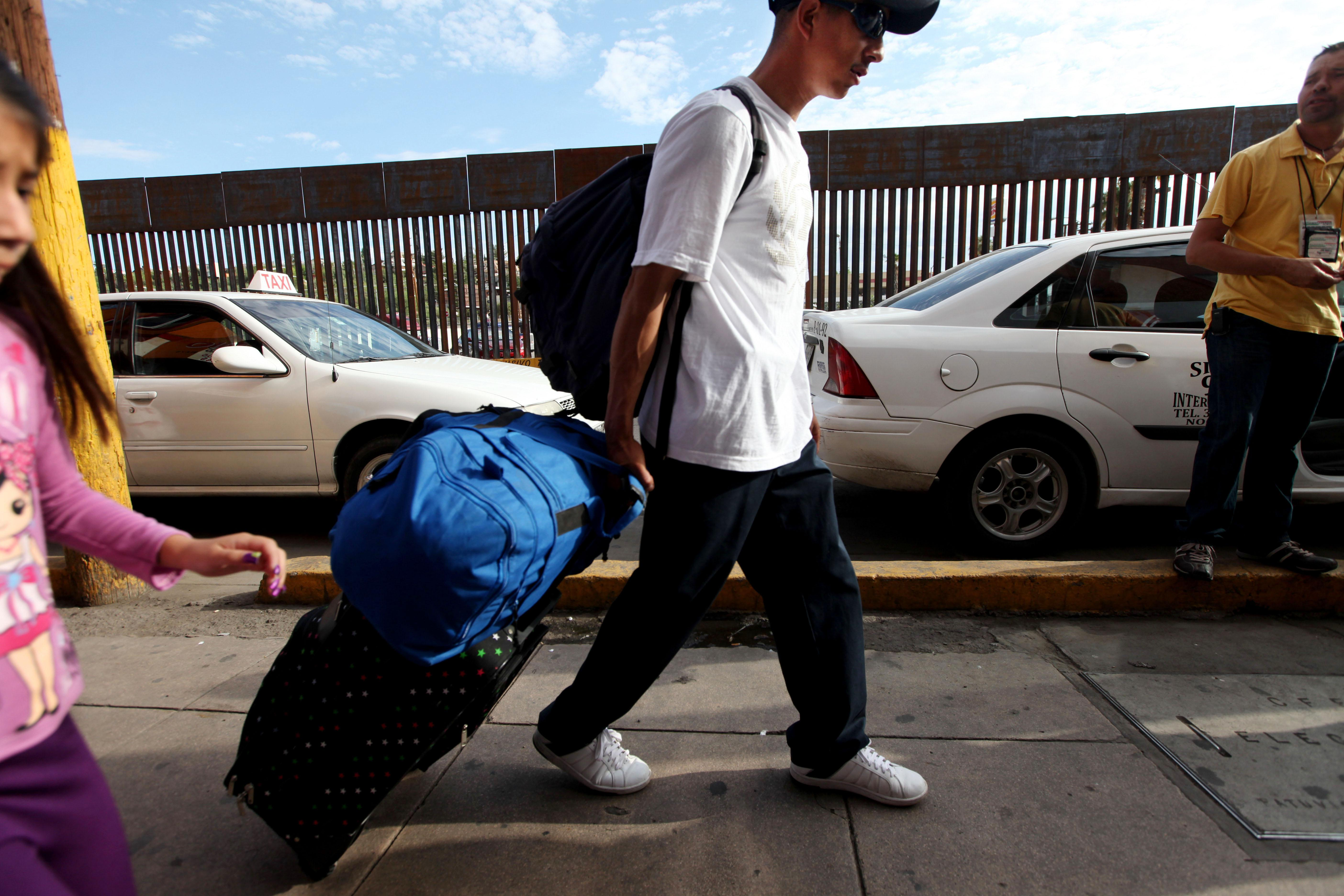 A Mexican national carts his luggage toward the U.S-Mexico border on July 7, 2012, in Nogales, Mexico.