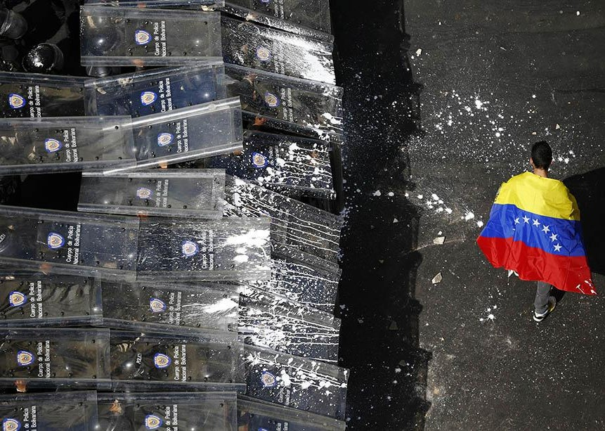 A demonstrator with a Venezuelan flag draped around himself protests against the government of Venezuela's President Nicolas Maduro.