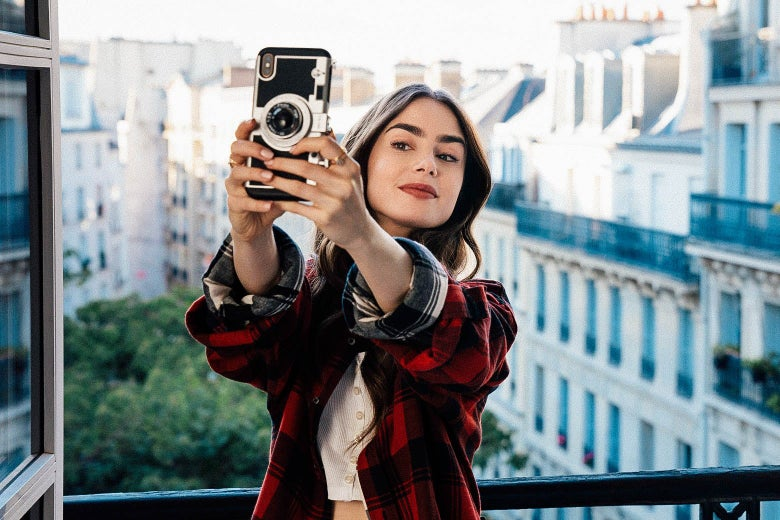 A young brunette takes a selfie on a Parisian balcony.