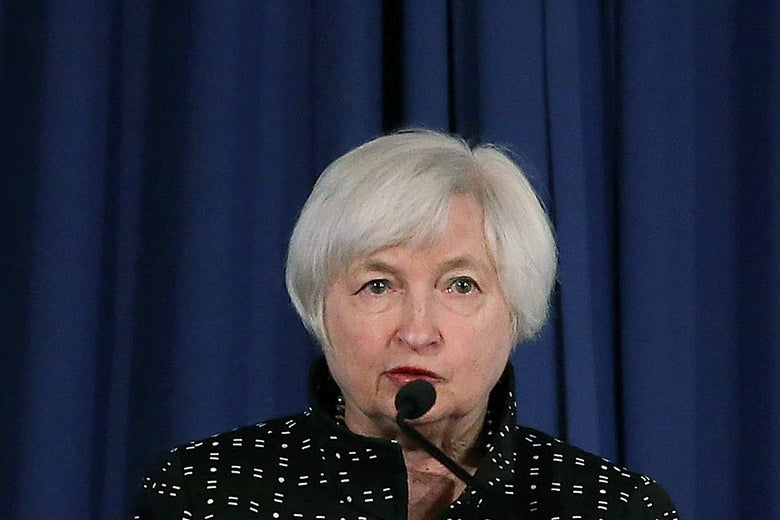 Janet Yellen speaks into a microphone against a blue curtain.