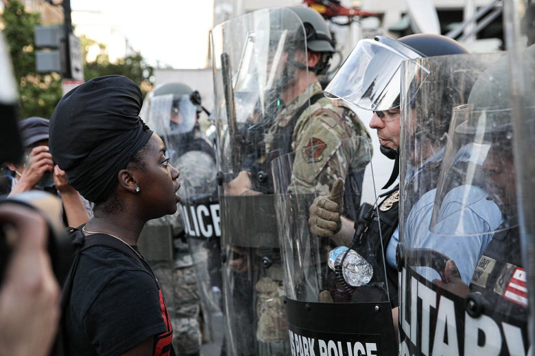 A protester directly faces officers who are carrying shields and blocking the road.