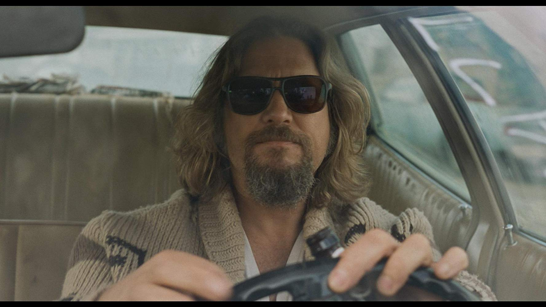Long-haired man with beard driving with sunglasses on and a tan sweater.