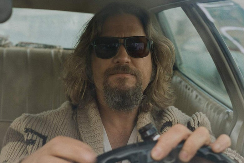 c71483c041 Long-haired man with beard driving with sunglasses on and a tan sweater.